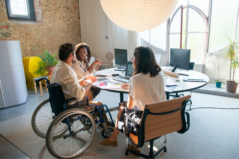 A group of young business professionals sit around an office table