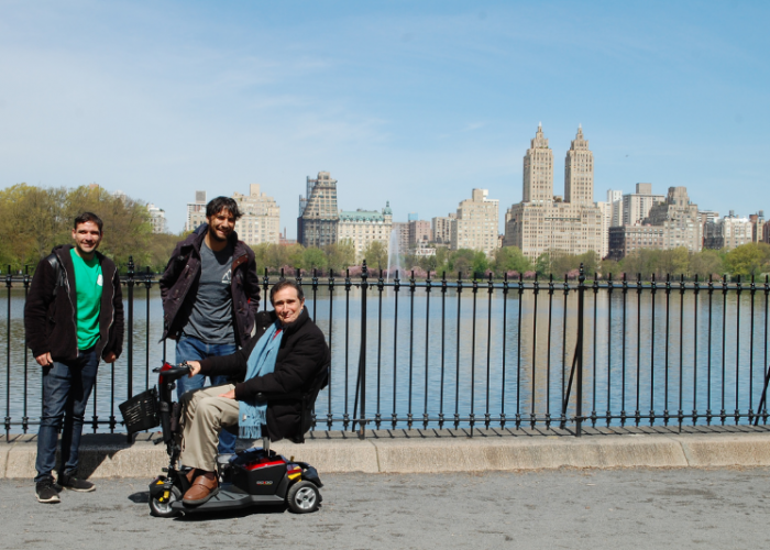 Three men, one in a power wheelchair, smile for the camera in front of a lake with city buildings behind it