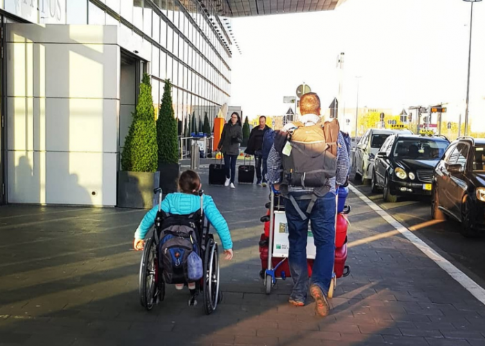 A girl in a wheelchair rolls next to her father, who pushes a trolley of suitcases outside of the airport