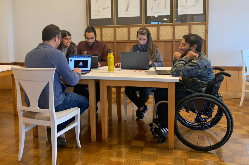 A group of three men and two women sitting at a table working on their computers. One man is in a wheelchair. One woman looks at the screen of the person on her right and smiles.