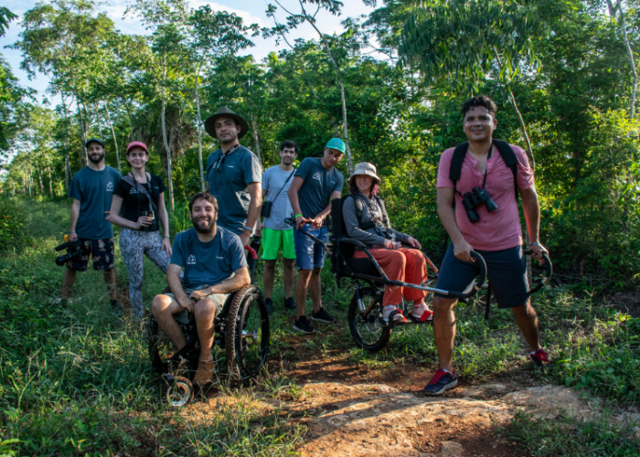 A group of travelers in the jungle smile for the camera while using adaptive wheelchairs