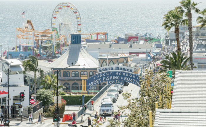 an overhead shot of the entrance to the Santa Monica pier. An arched sign over a street reads Santa Monica, cars drive underneath it. Just beyond the sign is a ferris wheel and various attractions on the pier over the water.