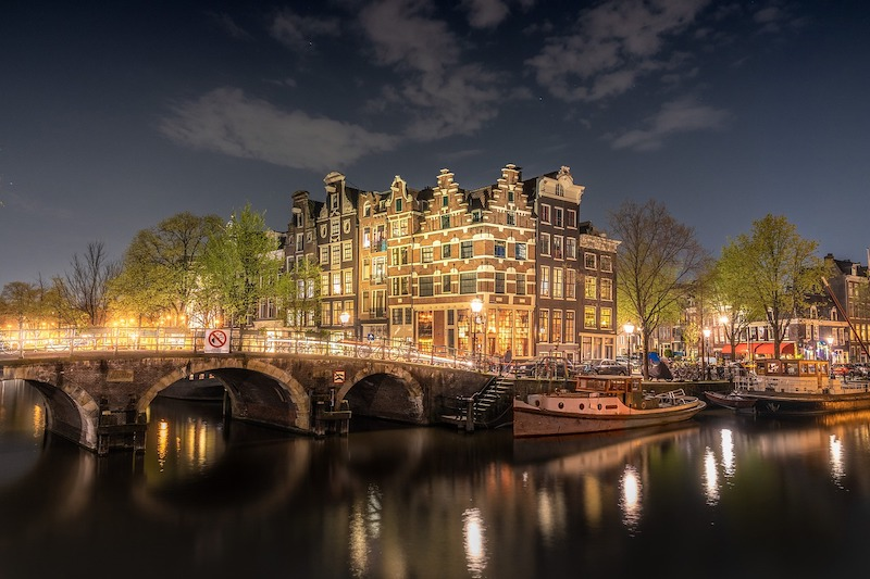 A lit bridge over a canal in Amsterdam