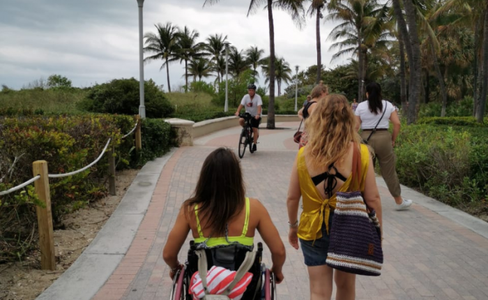 Two women, one in a wheelchair, stroll along the paved walkway that lines Miami Beach.